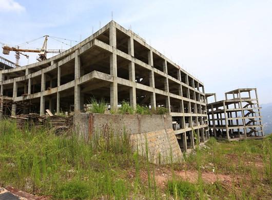 2015年7月25日,湖北省巴东县神龙溪片区铜鼓包居住组,占地2万余平方的巴东影视文化中心已经停工近3年,主体框架已经完工的行政中心和文化广场楼体与生锈的塔吊和建筑材料形成鲜明对比。大楼内部和周边的工棚人去楼空,杂草丛生。